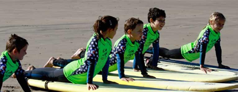 Niños practicando en la escuela de surf